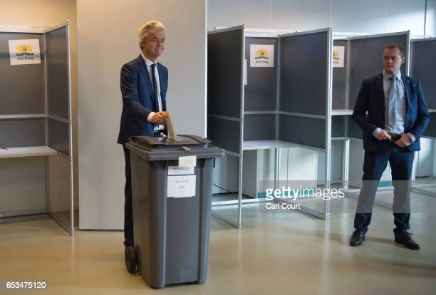 A close protection police officer looks on as Geert Wilders the leader of the rightwing Party for Freedom casts his vote during the Dutch general...