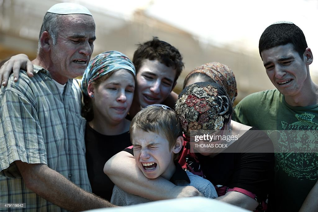 Close relatives of Malachi Moshe Rosenfeld, an Israeli settler who died in a car shooting attack near a Jewish settlement in the Israeli-occupied West Bank in which three other people were wounded, cry during his funeral in the Kohav Hashahar settlement, on July 1, 2015. The four Israelis' car came under fire late on July 29 near the Shvut Rachel settlement, and that it was unclear whether it was a drive-by shooting or a sniper attack.