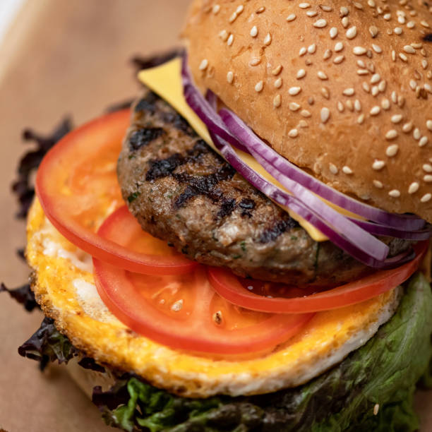 Close uf of burger with grilled meat. Fast food menu concept. Homemade Nutritious snack or lunch. Classic American food. Square format for posting on social media