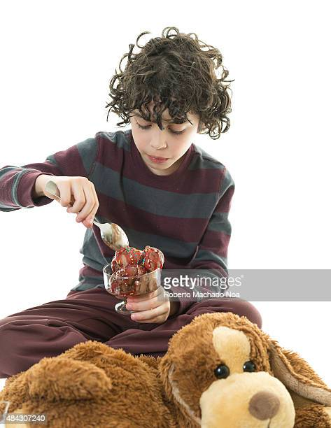Close up a young boy eating chocolate ice cream with a spoon in a glass cup against a white background Young boy holding chocolate ice cream scoops...