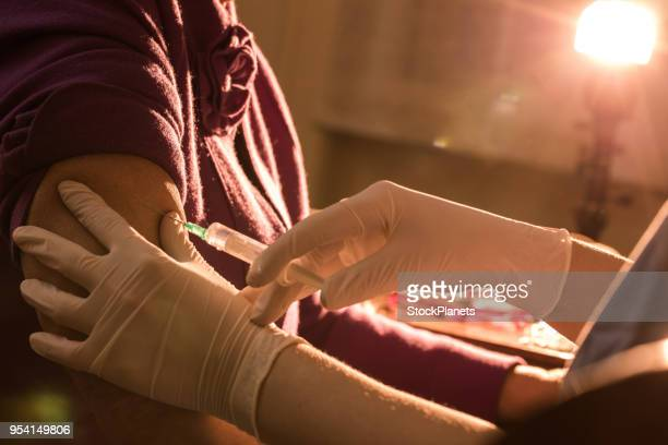 Close up adult women getting injection at home