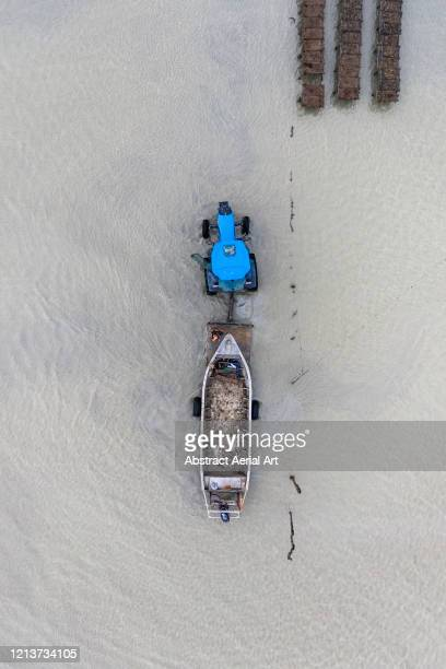 close up aerial shot of a tractor towing a boat from the ocean, france - ille et vilaine stock pictures, royalty-free photos & images