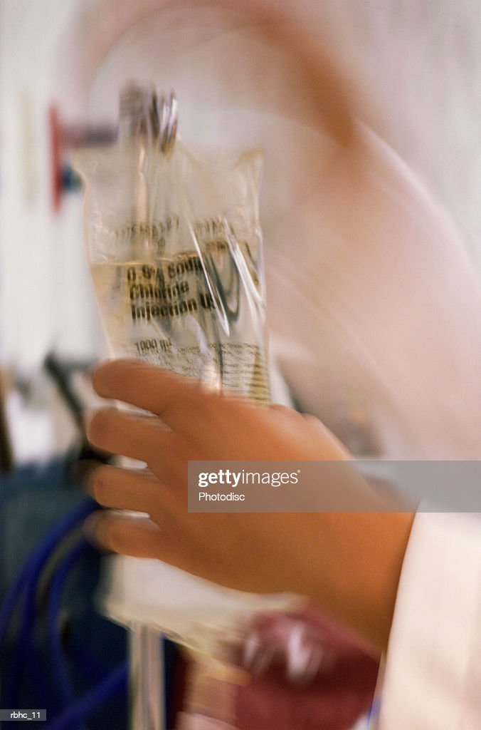 close up as a nurse places an iv bag on a pole : Stockfoto