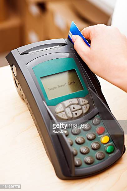 Close up as woman's hand swipes credit card through reader.
