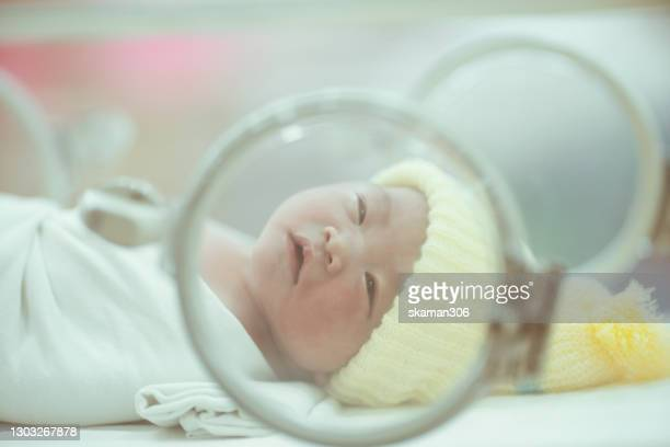 close up asian newborn baby  sleepy in an incubator first day - critical care stock pictures, royalty-free photos & images