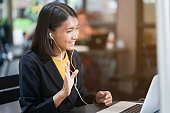close up asian woman use earphone connect to laptop and talking greeting by video conference with friends or family at outdoor coffee restaurant in relax time , lifestyle people concept