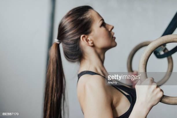 hautnah am fitness-frau, die durchführung der übung auf gymnastik ringen - frauen ringen stock-fotos und bilder