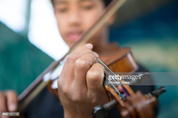 Close up at the hand of a young boy playing the violin