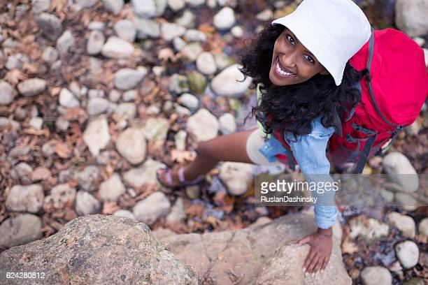 Close up backpacker woman walking on creek rocks.