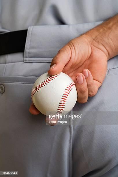 close up baseball pitcher holding baseball behind back - baseball strip stock pictures, royalty-free photos & images