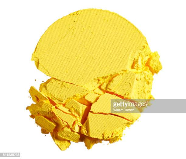 A close up beauty image of a smashed or broken yellow powder make up compact