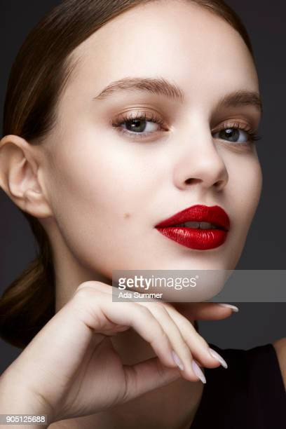 close up beauty shot of a woman wearing glossy red lipstick