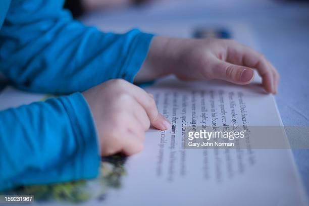 close up boys fingers pointing to words in book - reading stock pictures, royalty-free photos & images