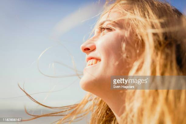 close up carefree, smiling woman enjoying sunshine - luz del sol fotografías e imágenes de stock