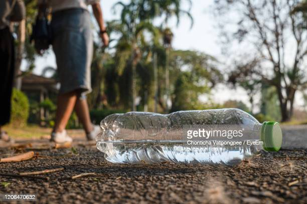 close up clear plastic bottle water drink with a green cap on the road in the park - bottle green stock pictures, royalty-free photos & images