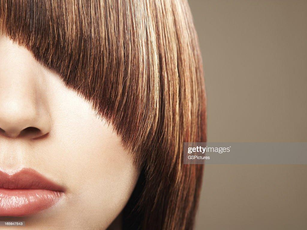 Close-up de mulher da corte franja coverin seus olhos : Foto de stock