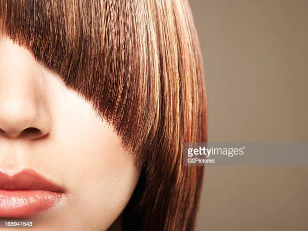 Close up crop of woman's bangs coverin her eye