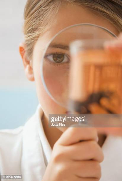 close up curious junior school high girl with magnifying glass - magnification stock pictures, royalty-free photos & images