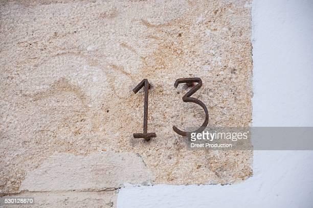 Close up detail house number wall thirteen metal