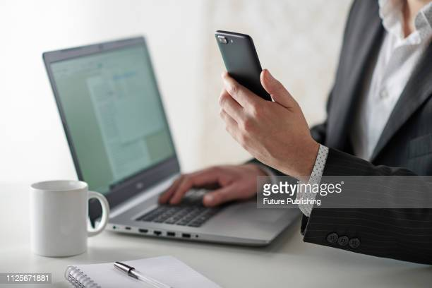 Close up detail of a businessman working at a desk with a smartphone and laptop computer, taken on January 31, 2019.