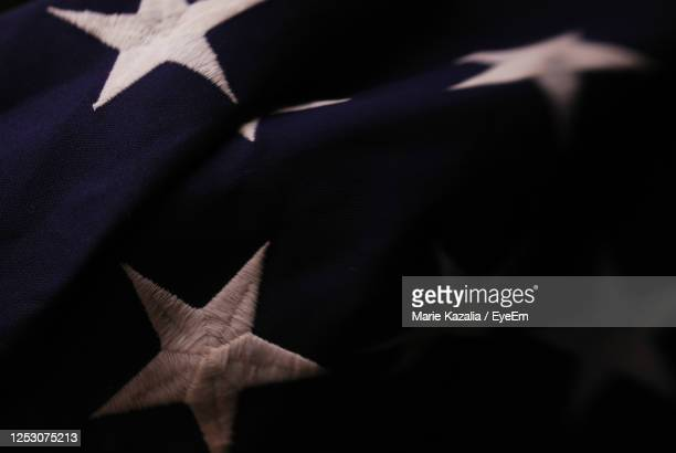 close up detail of a few white stars on blue field american flag - midsection stock pictures, royalty-free photos & images