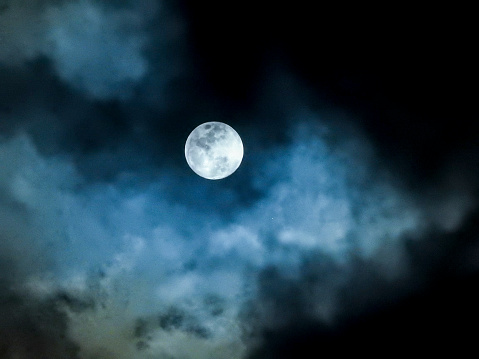 Close up detail of a full moon shining through bluish clouds - gettyimageskorea