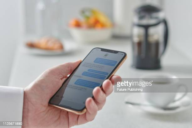 Close up detail of a man holding a smartphone over a kitchen counter, taken on January 31, 2019.