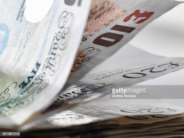 close up detail of a stack of british banknotes - british pound sterling note stock pictures, royalty-free photos & images
