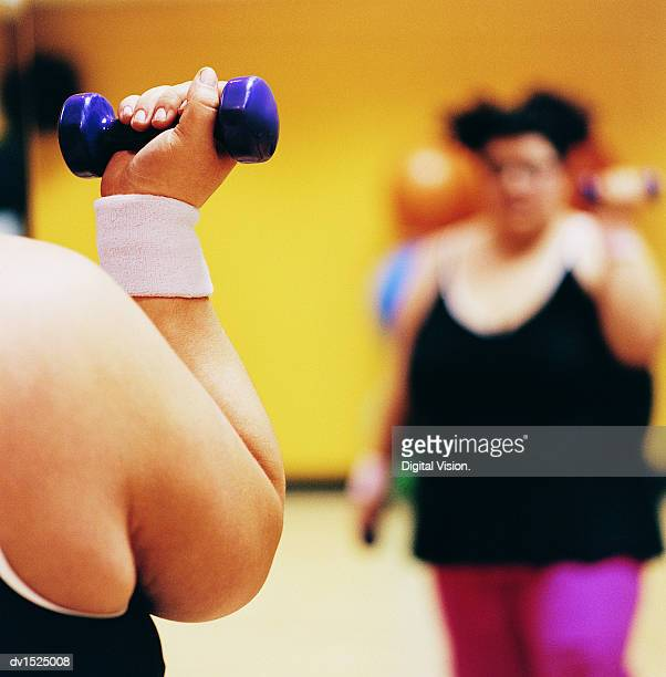 Close Up Detail of a Woman Doing Weight Training in a Gym