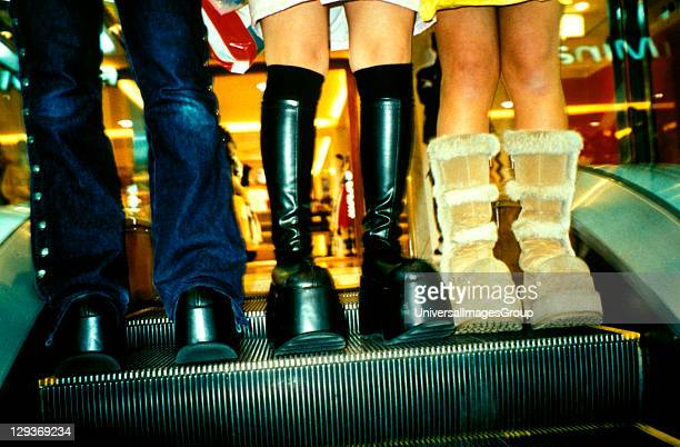 Close up detail of three pairs of knee high boots on an escalator Sapporo Japan 2000