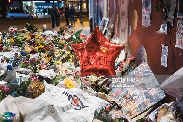 Close up details of Flowers letters and other tributes left on a mound continue to grow two weeks after the death of Brixton born English singer...