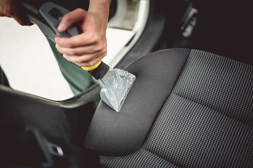 Close up details of worker vacuuming leather car interior 870884650