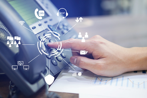 close up employee call center man hand point to press button number on telephone office desk with virtual communication technology concept 1011428626