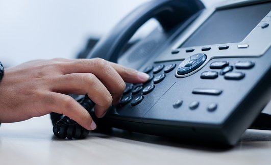 close up employee man hand point to press button number on telephone office desk for contact customer or colleagues in company .hotline employee concept 1050778742