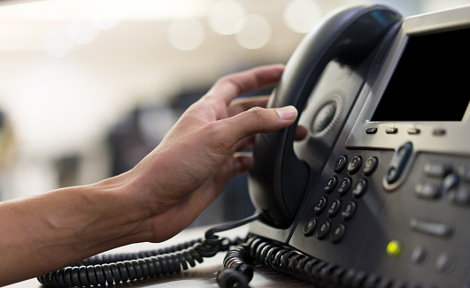 close up employee man hand touching handset of  telephone on desk for contact customer or receiving call , hotline  concept 1136541031