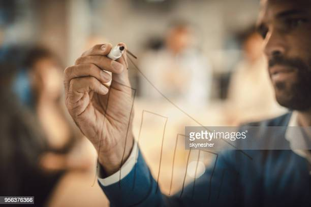 close up f businessman drawing progress graph on transparent wipe board. - performance stock pictures, royalty-free photos & images