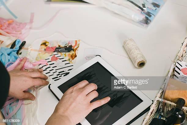 Close up female designers hands using digital tablet in design studio