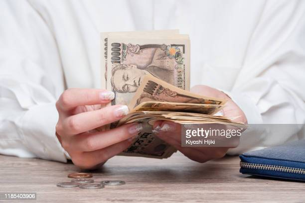 close up female hand counting japanese yen bank notes, concept of banking, saving, currency,financial - japan economy stock pictures, royalty-free photos & images