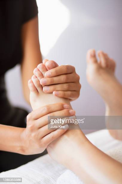 close up female masseuse massaging client's feet - foot stock pictures, royalty-free photos & images