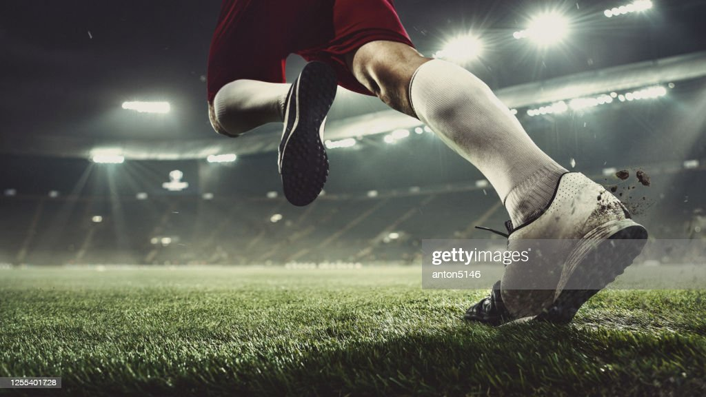 Close up football or soccer player at stadium in flashlights - motion, action, activity concept : Stock Photo