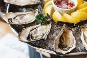 Close up Fresh Oysters and many kinds of fresh oysters served in round tray with slice lemon and spicy sauce.