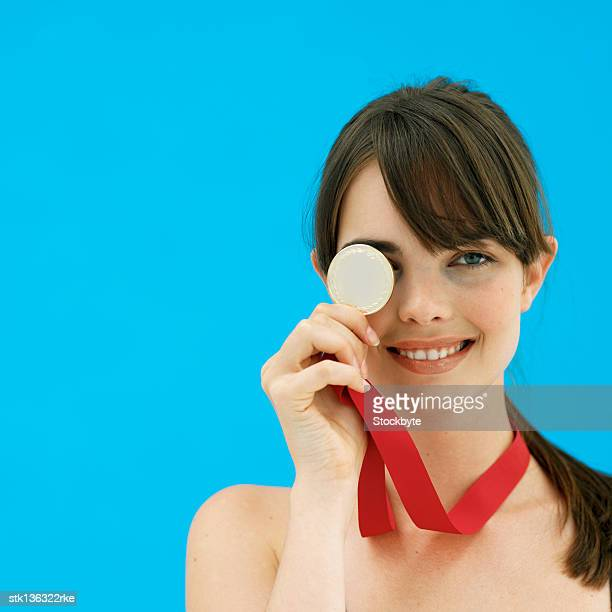 close up front view of woman holding gold medal - メダル ストックフォトと画像