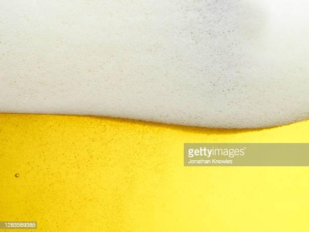 close up frothy beer head - ラガービール ストックフォトと画像