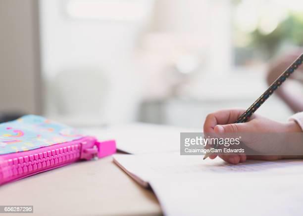 Close up girl doing homework with pencil