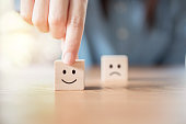 Close up hand choose smiley face and blurred sad face icon on wood cube