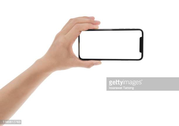 close up hand hold phone isolated on white, mock-up smartphone white color blank screen - horizontal stock-fotos und bilder