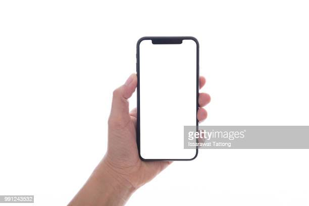 close up hand hold phone isolated on white, mock-up smartphone white color blank screen - cogiendo fotografías e imágenes de stock