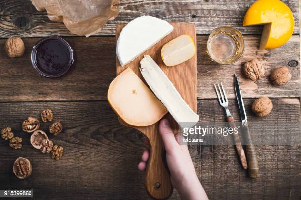 close up hand holding cutting board  with cheese - nut food stock photos and pictures