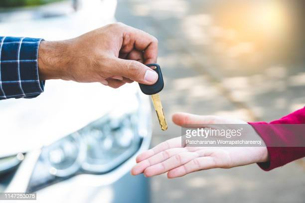 close up hand male giving a key new car on hand female outside her car. concept of rent car or buying car. - verkopen stockfoto's en -beelden