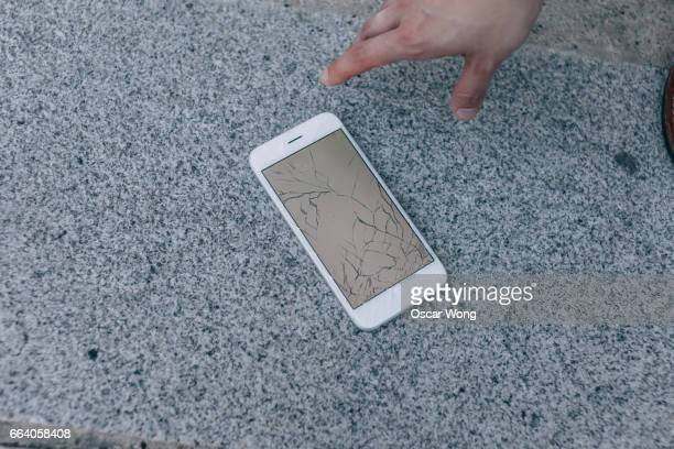 Close up hand picking up a broken mobile phone